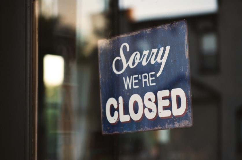 Sorry We're Closed on a Metal Sign in Shop Window