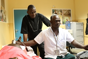 Dr Bittaye and senior trail midwife Mr Buba Jadama using ultrasound to measure the gestational age in pregnancy