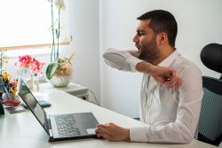man coughing in his elbow working at his desk