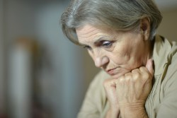 older woman not feeling well with head resting on hands