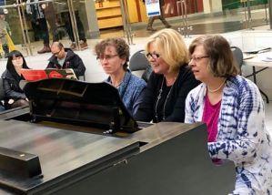Three teachers perform on the same piano at Musicthon 2019