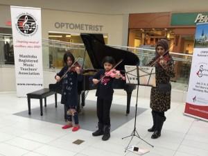 Three students playing violin at Musicthon 2019