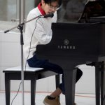 A student sings and plays piano at Musicthon 2020
