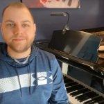 Teacher Corey sitting at his piano in his studio
