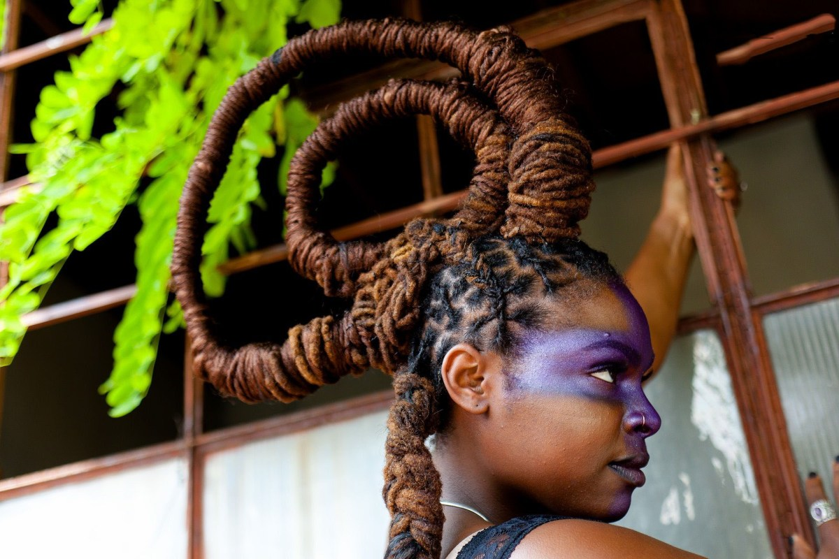 Woman with dreads styled into a looping crown facing right