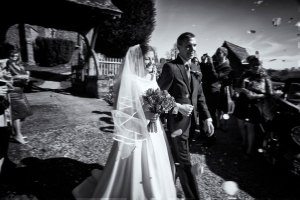 Black and White image of the wedding couple leaving the church