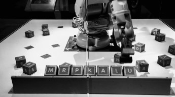 Image of a robot placing lettered blocks spelling MrPKalu on a stand