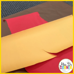 use construction paper or butcher paper to create fake flames for the fireplace.