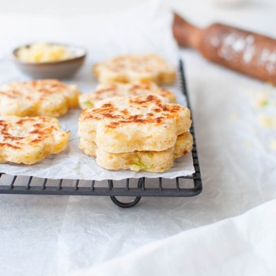 side shot of savoury welsh cakes piled on cooling rack with grated cheese in the background