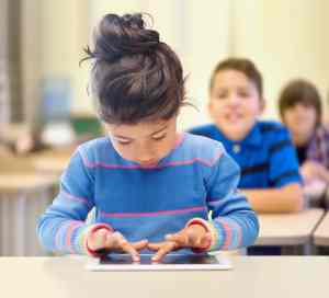 education, technology, students - little student girl with tablet pc over classroom and classmates background