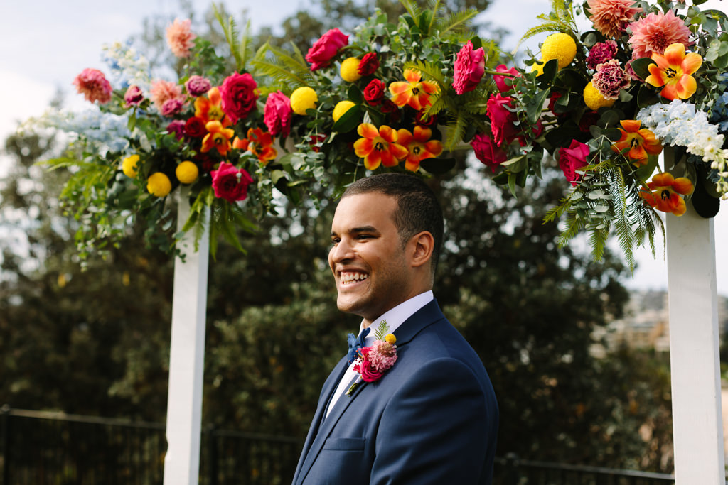 groom - white arbour with colourful florals - Tropical theme wedding - Gemma Clarke Photography