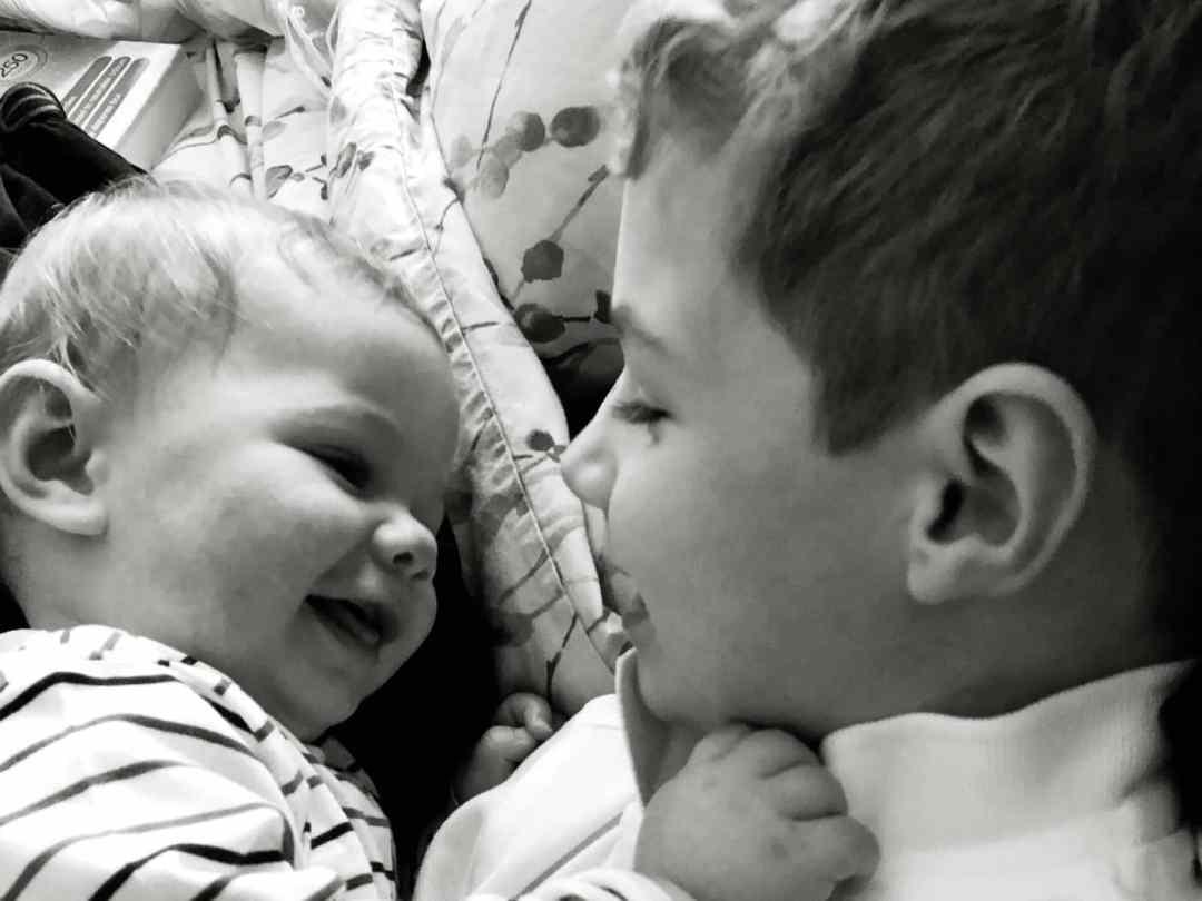 Brothers cuddles siblings