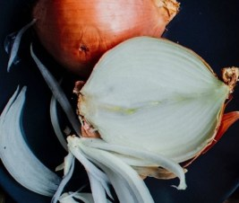 An onion cut in half with brown outer skin still on.