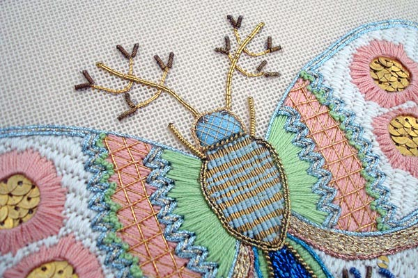 This needlepoint butterfly is a highly stylistic depiction, a blend of stitches and thread types.