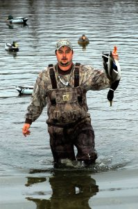 Nick Quinn retrieves a mallard drake he downed in a wooded slough while hunting over mallard decoys.