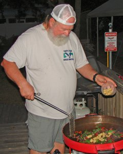 The author adds ingredients for stir fry king mackerel into his FireDisc cooker.