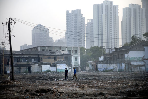 Workers look for salvageable materials in rubble caused by the destruction of hutongs, or traditional Chinese residential alleys, in central Tianjin, China, to make room for modern high-rise building construction.