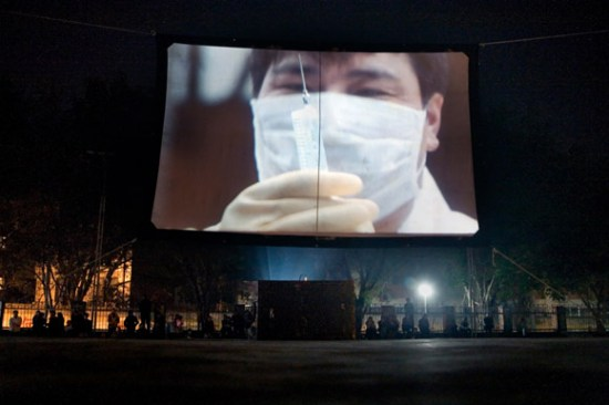 A public service film about medicine, health, and hygiene, plays on a temporary screen in a park in Hekou, Yunnan Province, China, on the Vietnam border.