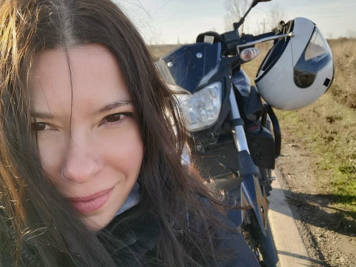 a white woman with long brown hair is in front of her motorcycle