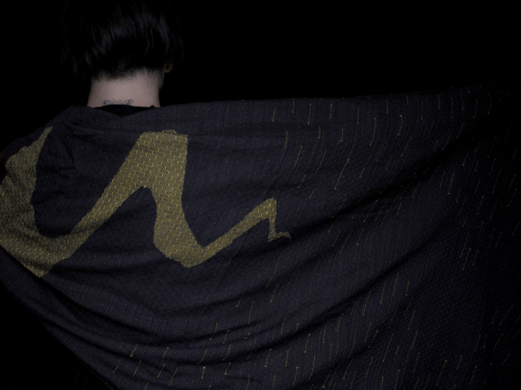 image of a white woman wearing black with a blak and gold ring sling worn as a shawl . The design is a mamba slithering across the cloth
