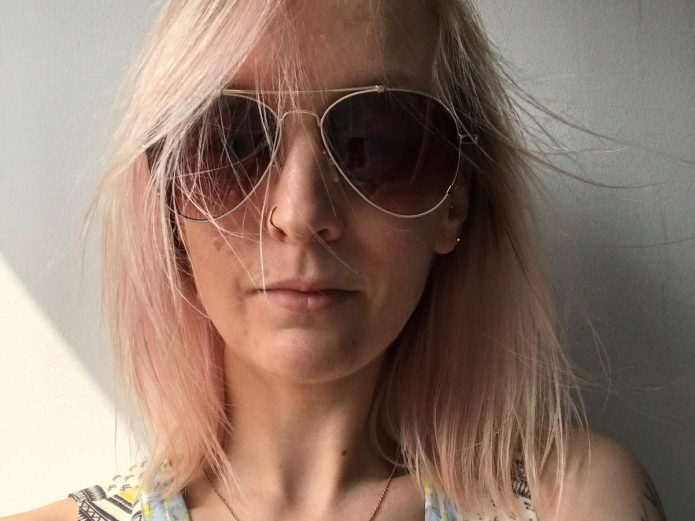 image of a white woman with shoulder length blonde hair. She is wearing sunglasses