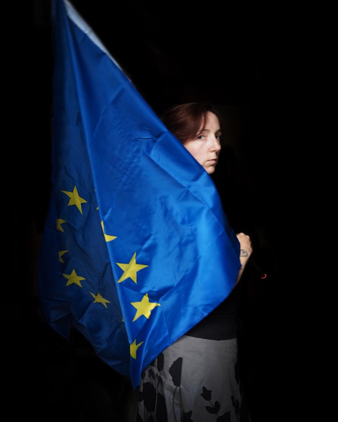 image of a white woman carrying a large EU flag