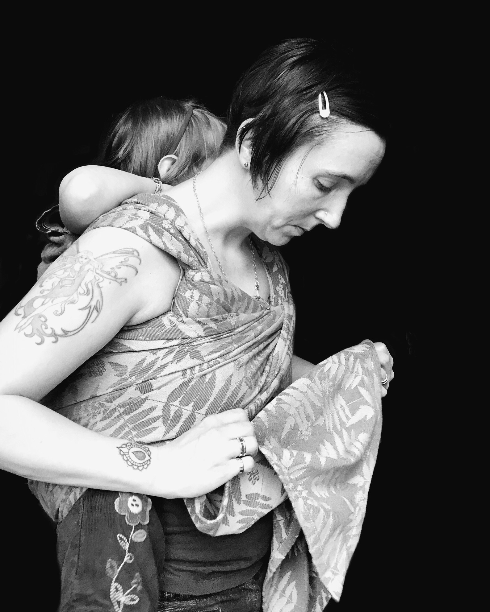 Image of a woman with a young child on her back. She is studying the wrap