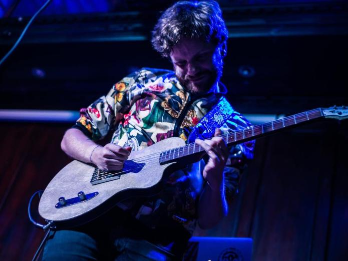 image of a white man wearing a vibrant shirt who is playing a bass guitar
