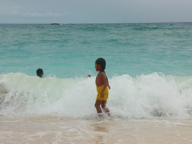 A kid playing with the strong waves in Malapascua