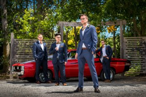 Groom and groomsmen posing in front of a car