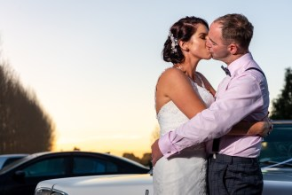 Newlyweds kissing on sunset