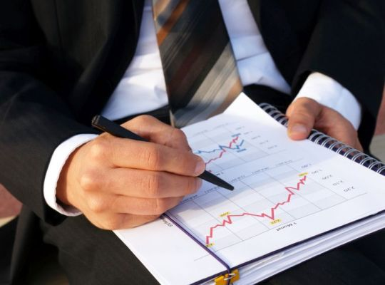 Man with a journal reviewing a sales cycle for his business