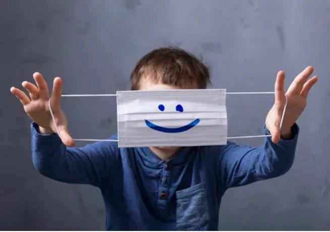 Foto de un niño sujetando una mascarilla delante de su cara que ofrece dibujada una gran sonrisa