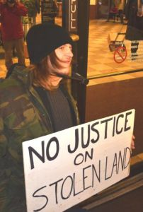 "Protestor holding sign saying ""No justice on stolen land""."