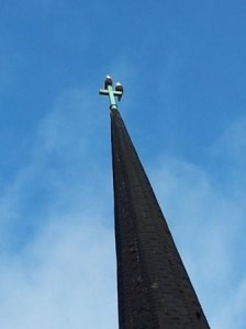 Two eagles on a cross on a steeple.