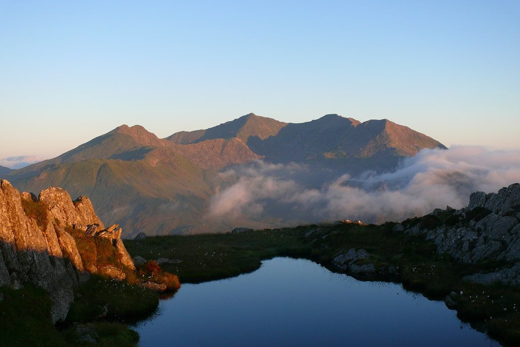 Llyn bach ar Garnedd y Cribau gyda haul y wawr yn lliwio'r Wyddfa / A small lake on Carnedd y Cribau with the sunrise colouring Snowdon. © Copyright Ian Medcalf and licensed for reuse under this Creative Commons Licence