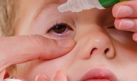 child getting eye drops