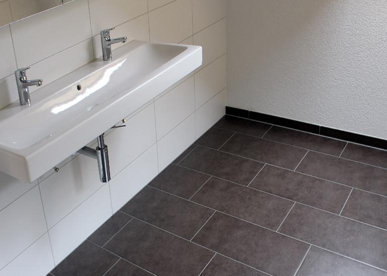 Badezimmer mit hellem und dunklem Plattenbelag
