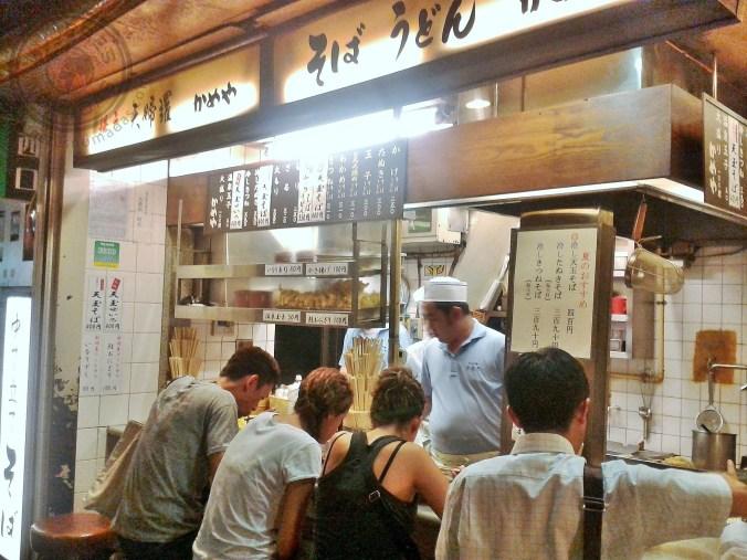 Cenando en la barra de un restaurante en plena calle en Tokio