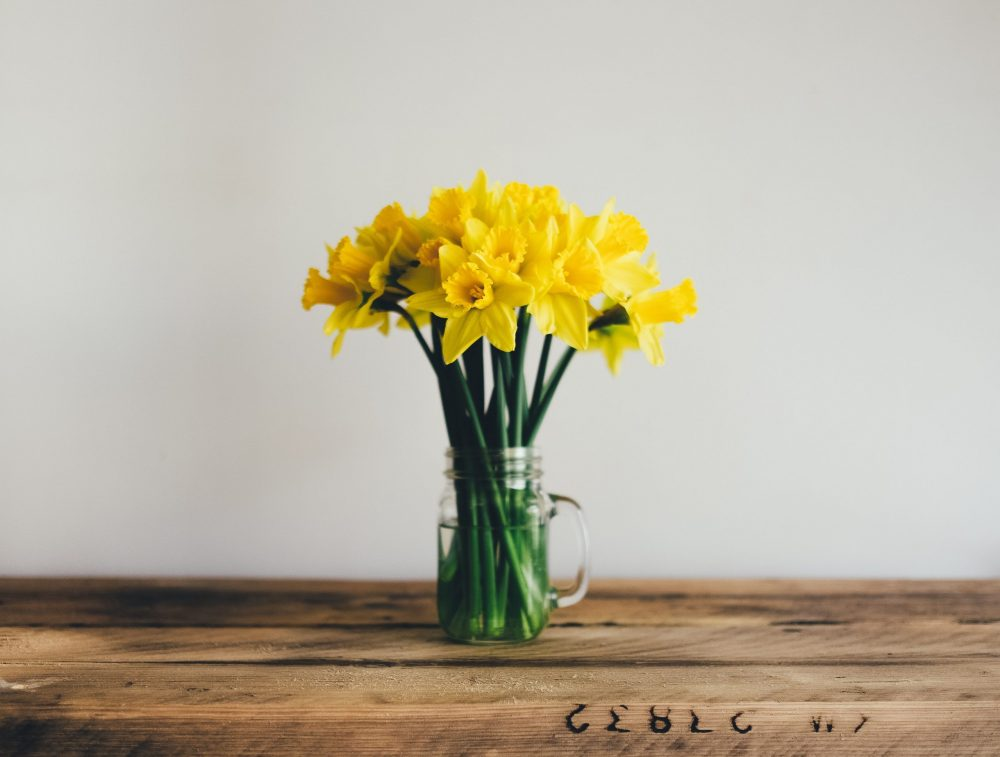 A bunch of daffodils sits in a clear mason jar on a wooden table