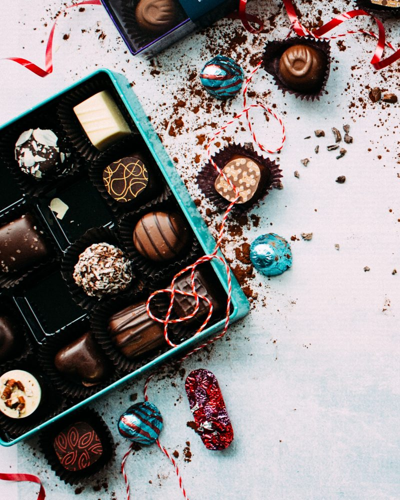 A large box of chocolates is open, some have spilled out on tot he table and there is red and white string laying on the top