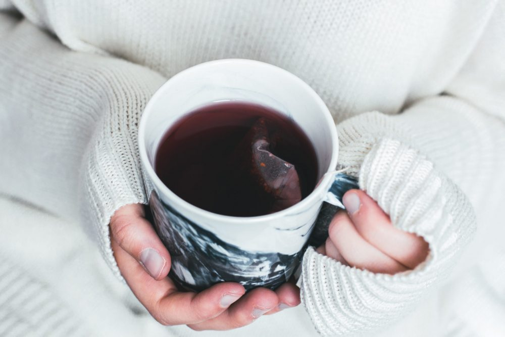 Hands in a white oversized sweater hold a mug of herbal tea that looks like Roobush. The teabag is still in the tea