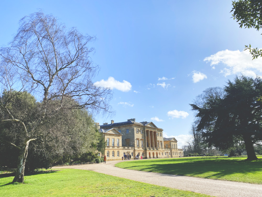 A sideways look at Basildon Park National Trust house in the distance. The sky is blue and the grass beautifully cut and bright green