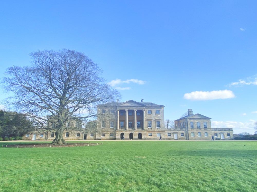 The front of Basildon Park National Trust house sits against a blue sky, and green sweeping lawns