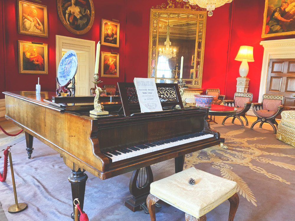 A large piano sits in a heavily furnished room with red walls at Basildon Park National Trust house