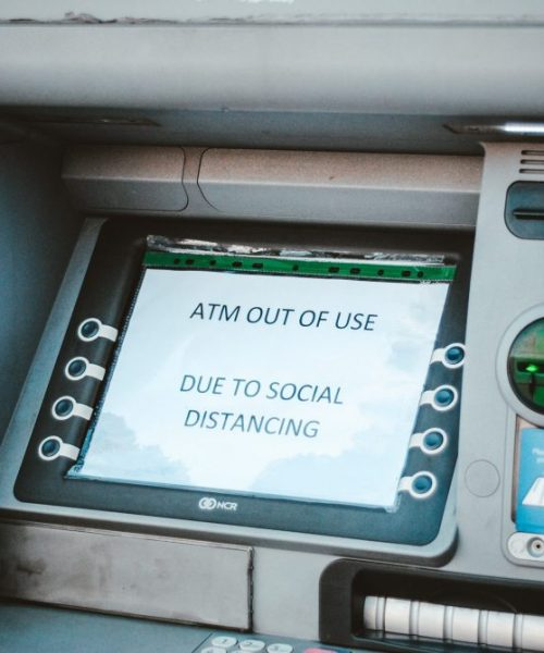 An ATM machine displays a sign saying ATM out of use due to social distancing