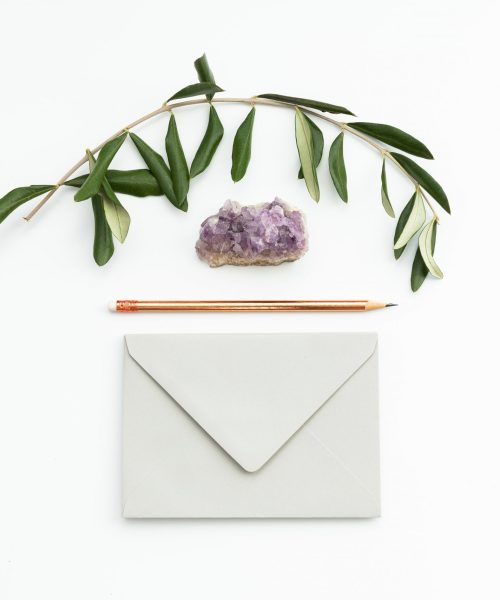 Flat lay of a purple crystal, an envelope, a pencil and a sprig of leaves