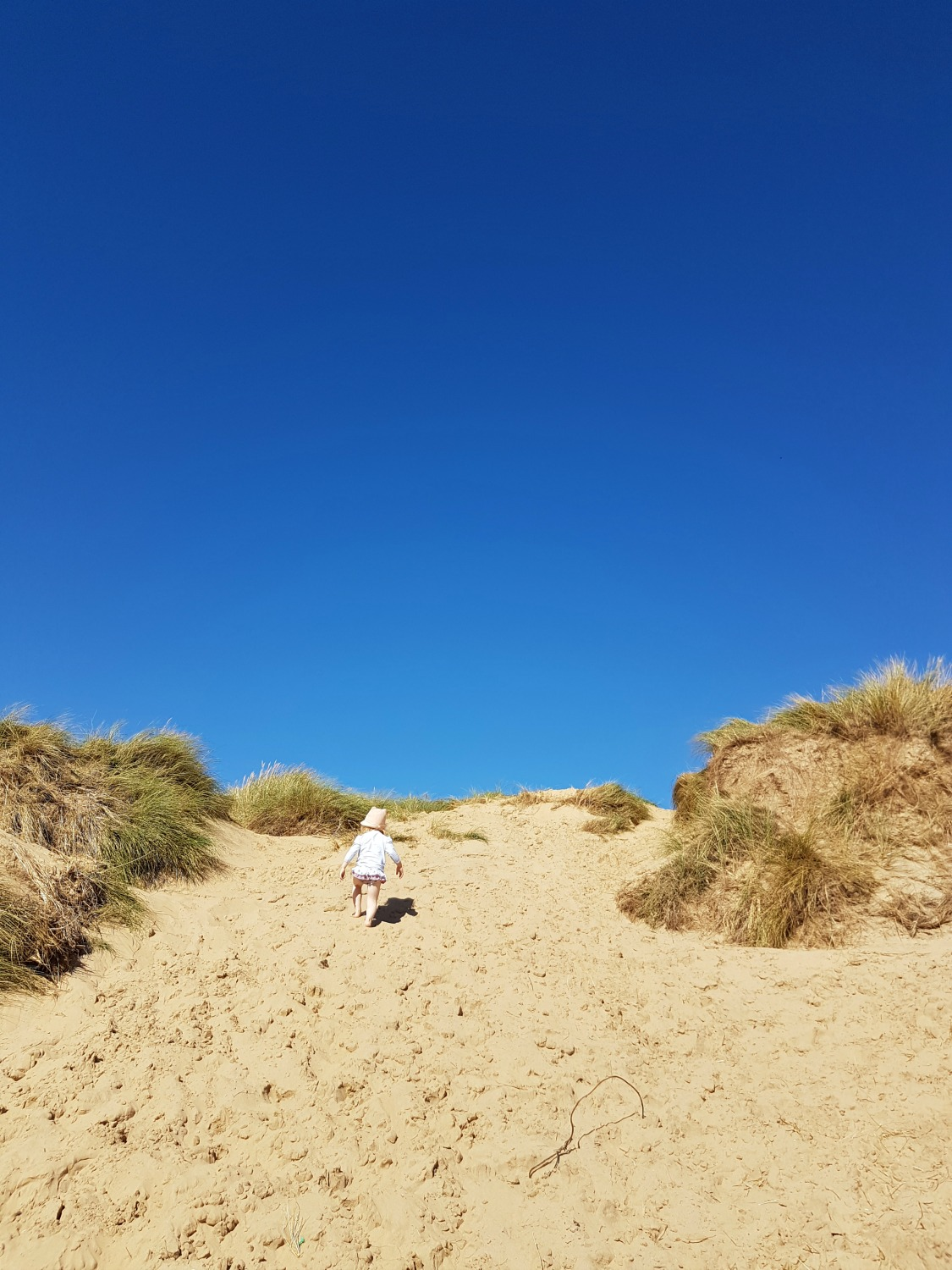Girl on the dunes at Camber Sands beach in East Sussex - spending a weekend in East Sussex with my daughter before the start of school, to explore the history and coastline
