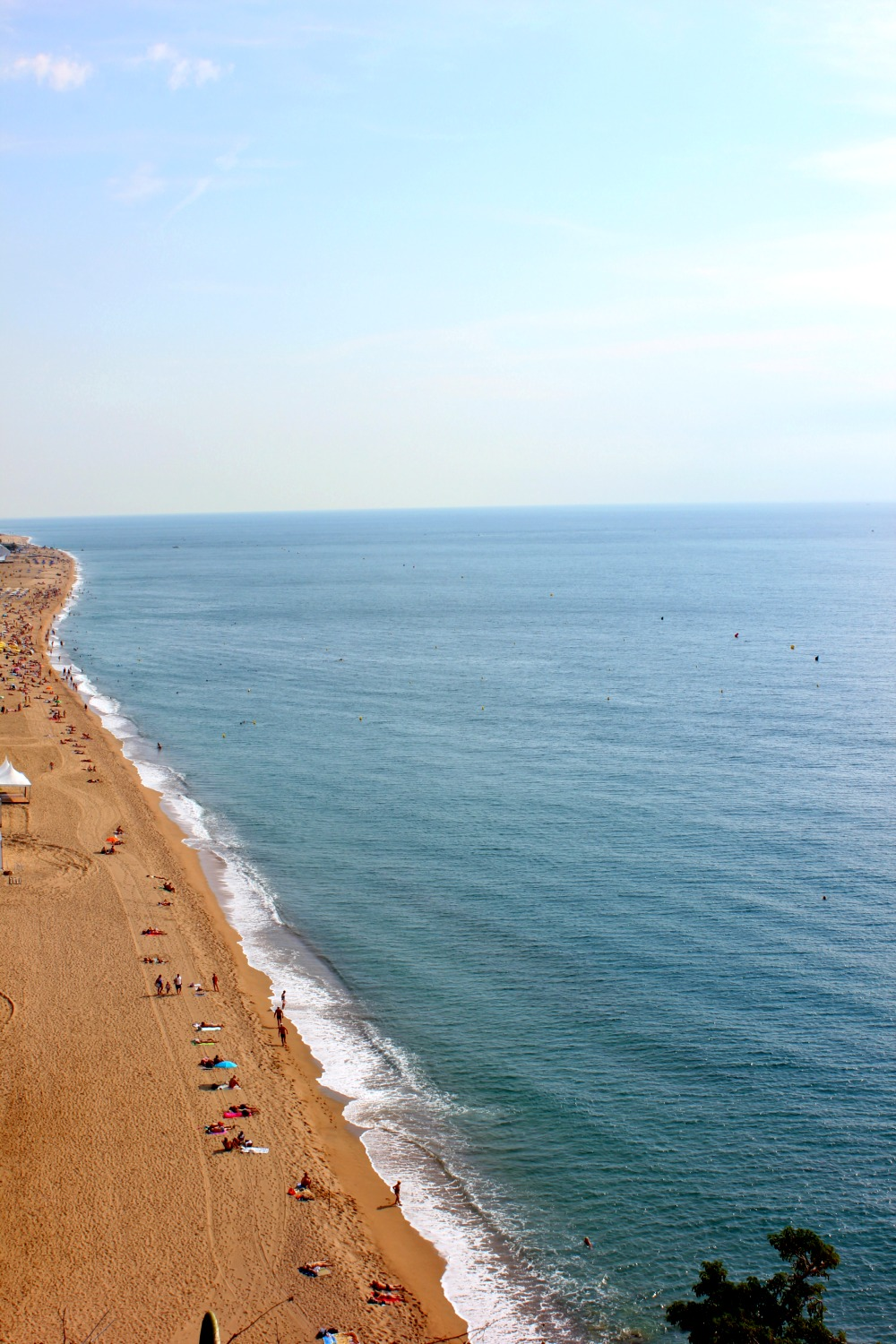 View of the beach at Calella, a long stretch of golden sands against the blue of the Mediterranean - how to spend one day in Calella, Costa Barcelona, Spain