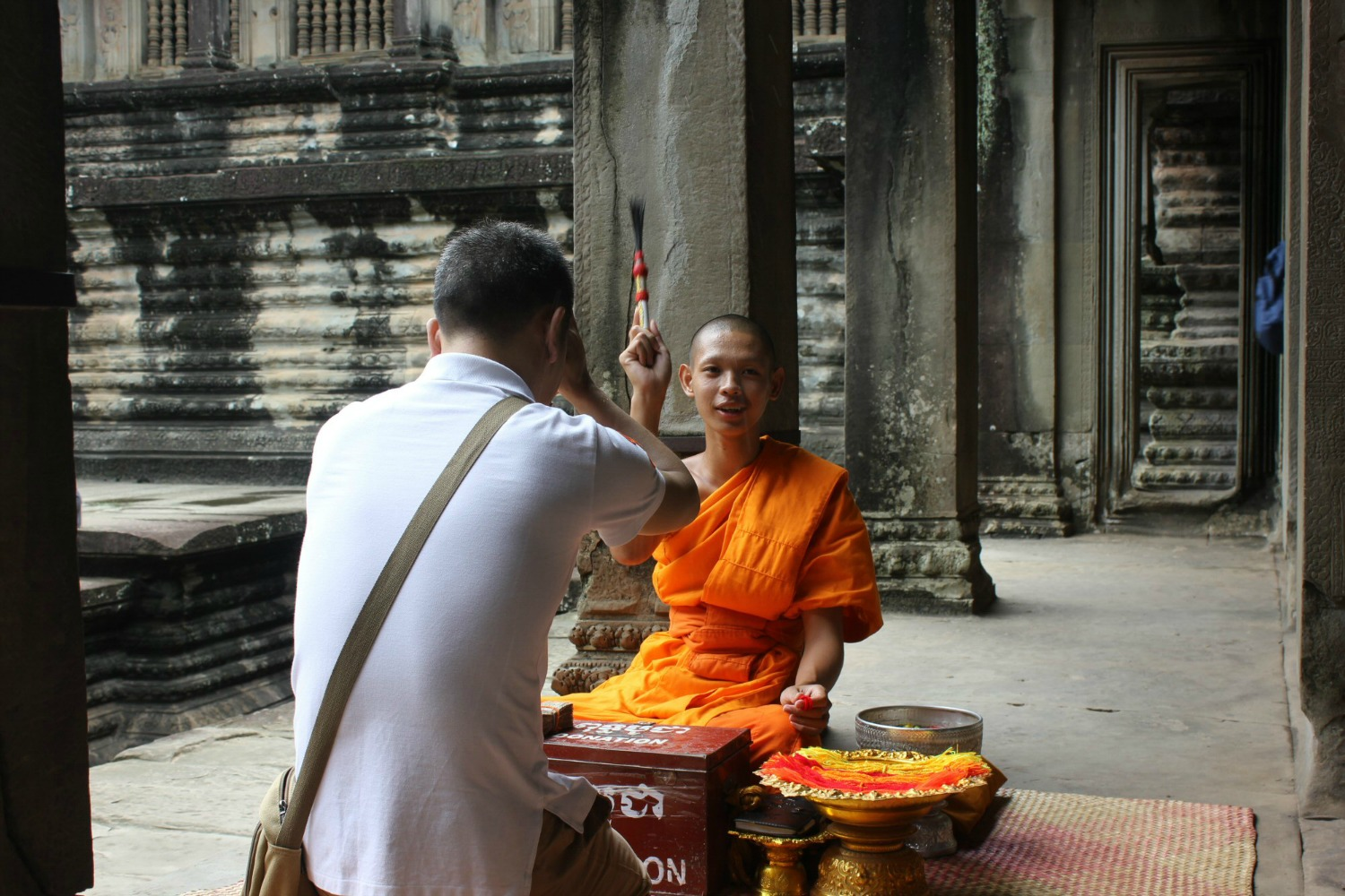 A monk blesses a man at Angkor Wat - my 12 reasons to visit Cambodia with kids